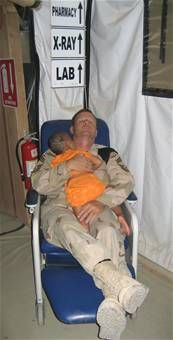 Chief Master Sgt. John Gebhardt cradles a young Iraqi girl as they both sleep in the hospital. The girl's entire family was executed by insurgents. The killers shot her in the head but she survived. The girl received treatment at the U.S. military hospital in Balad, but cries often. According to nurses at the facility, Chief Gebhardt is the only one who can calm down the girl, so he holds her at night while they both sleep in a chair.