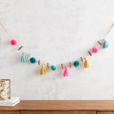 Think outside the frame with our unique clip strand, crafted with a rustic jute rope, fir clips and whimsical cotton tassels. Hang it from walls, mantels, bed frames and more to display nine of your favorite photos.