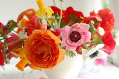 Photo By Chelsea Fuss  This centerpiece is stunning - mainly because of the vibrant blooms!        Materials:   10 red, white and pink anemones  5 mini daffodils  8 orange, red, and white ranunculus (better if blown open)  Ranunculus greens and buds  English daisies in pink and white (cut from 2 plants)  Modern vase  Rocks  Chicken wire or a flower frog  Clippers   Directions:  First, fill the vase ...