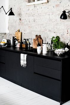 {Black shelving, white wood floors and white brick walls.}
