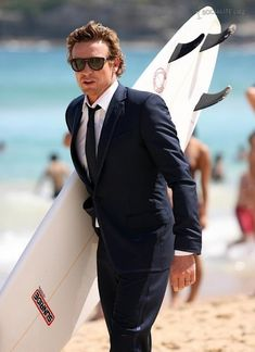 Simon Baker. Only an Aussie would sport a surfboard as an essential accessory! J:)
