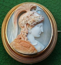 Shell cameo, ca. 1860, Italy, cameo: 2 x 1 3/4, frame: 2 3/8 x 2 1/8, carved in very high relief to depict the head of the goddess Athena, within elaborate and superb gold frame. This rare cameo of unbelievable quality seems extremely similar to an agate cameo carved by Tommaso Saulini,