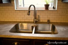 Undermounted sink with laminate countertop and subway tile.