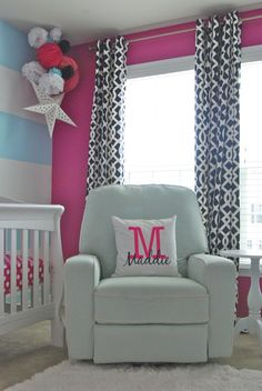 This nursery is not afraid of color with a hot pink accent wall!