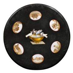 ROUND MICRO-MOSAIC PLATE, Restauration, Rome, ca. 1830/50. Black marble, finely inlaid with 7 micro mosaic medallions depicting the Piazza San Marco, the Colosseum, the Forum Romanum, the Via Antica, the Pantheon and the Temple of Vesta; the centre with a depiction of Hadrian's bowl with doves. Dim: D 90 cm. H 4 cm.