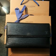 Louis Vuitton Epi Porte Tresor long trifold wallet NO TRADES! Authentic Louis Vuitton black Epi trifold wallet. Good used condition. The inside is very clean, looks brand new. No rips. The outside epi looks fine from a distance but up close under the light there are alot of scratches. The corners are gently worn. Worn on front above where the snap is. Comes w/ vintage bag, box and wrapping. Date code ca0072. Good from a distance, up close signs of wear. See addl listing. NO BUNDLE DISCOUNT…