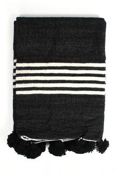 The Wool Stripe Pom Pom Blanket in Black, a cosy monochrome stripe blanket embellished with black wool pom pom trim. These traditional Moroccan blankets are adapted by Bohemia to create a contemporary