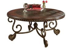 Rafferty from Ashley Dark stained wood round cocktail table with a nailhead trim will enhance your living room