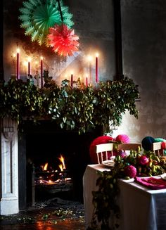Foliage and candles on the Christmas fireplace and dining table. For more like this, click the picture or see http://www.redonline.co.uk