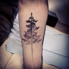 Watercolor black and gray tree tattoo on forearm