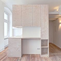 A pine unit provides a kitchen, bathroom and mezzanine level for this tiny Berlin apartment designed by two local architects, which also features Art Deco details including a parquet door. Photograph by Ringo Paulusch. See more micro apartments on dezeen.com/tag/micro-apartments #interiors #interiordesign #apartment #Berlin