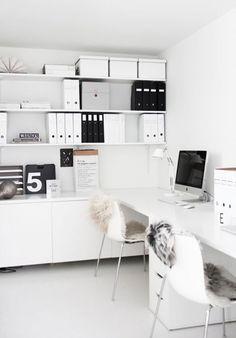 Oficina con mesón escritorio blanco, dos sillas blancas, repisas con archivadores blancos y negros y cajas blancas de cartón.