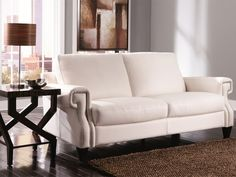 The sophisticated Zola Sofa has a contemporary, low profile silhouette with rolled arms, accented by silver nail head detailing.