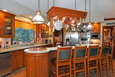 Kitchen island with a custom hanging pot rack, bar seating, a sink and built-in range.
