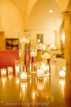 DIY wedding decor: Tall cylinder vases, filled with water, topped with floating candles. Gives off warm and inviting light.