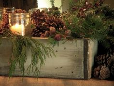 Charming! Love the candles in Mason jars! Display in an old wooden/distressed box; evergreen branches (steal from the back side of your tree), mason jars, pine cones, add lots of greenery,  cream pillar candles, pine cones and red berries...