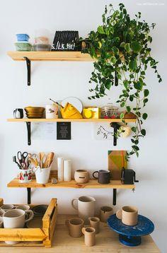 Ateliê de cerâmica com plantas e prateleiras de pinus com mão francesa preta.