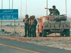 American Marines stand beside their humvee next to a road sign greeting visitors to Al-Khafji following the first major ground conflict with Iraqi forces on the Saudi-Kuwait border during the Gulf War, Jan. 30, 1991.