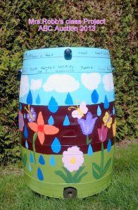 """Painted Rain Barrel"" Mrs. Robb–2nd Grade EAP   Mrs. Robb's 2nd graders' focus this year is on saving the much overlooked water resource–rain water. Their painted rain barrel would make your gardening a step more green. The built in planter allows you to add a touch of nature and beauty to your rain barrel which is equipped with a durable brass spigot with hose hook-up and a screen to keep out debris and insects.  School class auction project."