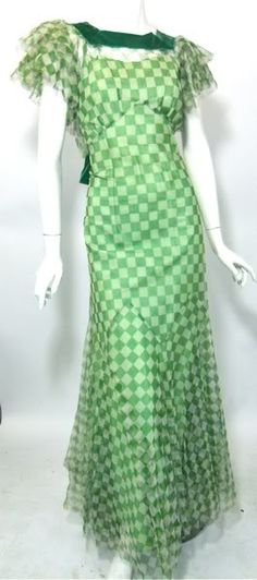 "Soft mesh gown (front) done in a checkerboard design in kelly green and white, c. 1930's. Collar trimmed in wide green velvet ribbon, velvet edging the plunging ""V"" in back with low bow. Layered ruffled sleeves and tiered skirt."