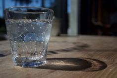 Bubbles - Sparkling water in a glass #bubbles #glass #shadow #Sparkling water #wooden table