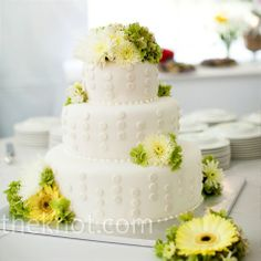 For a modern twist on a classic design, white-on-white fondant polka dots decorated Mailee and Brent's three-tiered wedding cake while yellow gerbera daisies added some color.
