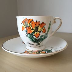 """Royal Grafton Vintage Teacup and Saucer  Gorgeous orange tiger lilies with green leaves adorn this teacup and saucer. In script it says """"Tiger Lily"""" and """"Emblem of Saskatchewan"""". This is the provincial flower of the province of Saskatchewan, Canada. This set is trimmed in gold and would make a great souvenir. Made In England Fine Bone China Back Stamp dates: 1957+  Measurements: Cup: 7.6cm high 8.1cm across(not including handle) Saucer: 14.3cm across  This set is in Excellent Used Condition…"""