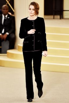 Kristen Stewart walks in the Chanel Haute Couture show wearing a black Chanel suit