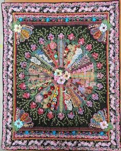 One of the great things about crazy quilting is that there really are no rules - a little embellishment or something completely over the top - it's whatever makes you happy.  This exuberant wall hanging is just covered in ribbon embroidered flowers, lace appliqué, buttons and beads.  It's the work of Nina Lazar of Liege, Belgium.  Check out her blog at http://ln-scrap-mania.blogspot.ca/