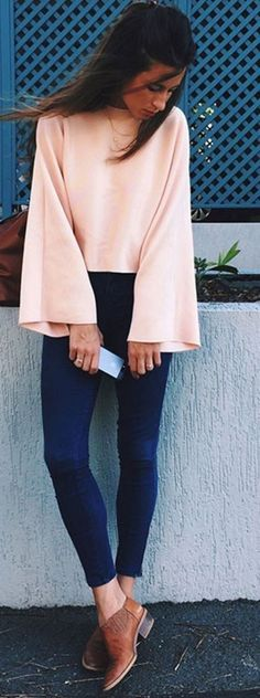 Pretty blush bell sleeved blouse with blue skinny jeans and tan booties.