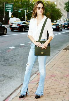 Alessandra Ambrosio wears a button-down blouse, distressed flare jeans, a shoulder bag, round sunglasses, and Christian Louboutin studded booties