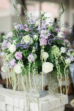lush ceremony arrangements in shades of purple, white and green / photo by Brooke Images
