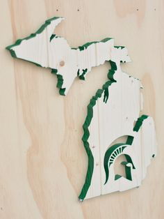 A beautiful handmade/hand cut wood silhouette of Michigan with the Michigan State University Spartans logo cut into it. It is 13x14.5 and is hand cut from 3/4 solid pine. Absolutely no plywood is used to ensure a uniform look to all exposed surfaces. It is cut from edge glued pine with additional routed grooving to further accentuate the pieces and their grain pattern. They are individually cut with an attention to detail. As they are individually made, the knot and grain patterns may vary…