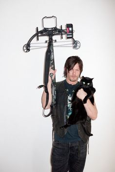 Norman Reedus (Daryl Dixon) from The Walking Dead holding his cross bow and a cat. Description from reddit.com. I searched for this on bing.com/images