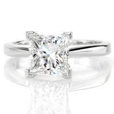 The Princess Classic Solitaire proudly displays a 1.50 carat diamond. Raised high above the mounting for an impressive statement this diamond takes center stage. V-tip prongs protect the edges of the square stone and lends a decorative detail. Pinched shoulders adds contour and dimension to the band.