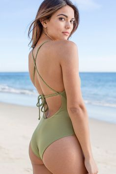 Frankies Bikinis Camo Green Poppy One PIece. The front and center of this adorable crochet one piece swimsuit is will get you tons of compliments, with it's unique design. The braided ties add a touch of luxury to this fabulous designer swimsuit. This one piece swimwear style ties in the back with criss cross straps, and offers cheeky backside coverage showing off just the right amount of skin. Please use the size chart to determine your best fit! Throw a pair of cut off jean shorts over top...