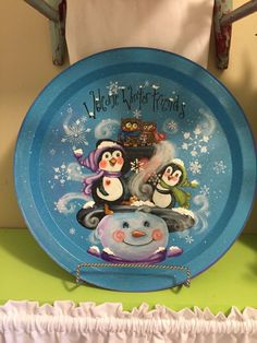 I hand painted a Snowman with penguins on a round tin plate that measures The background is turquoise with snowflakes and the words, Welcome Winter Friends at the top. It has snow texture on several places on the hat, penguins, and mittens. Christmas Snowman, Christmas Crafts, Christmas Ornaments, Painted Plates, Hand Painted, Decorative Painting Projects, Snow Texture, Penguins And Polar Bears, Welcome Winter