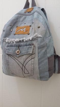 Mochila jeans customizada com 2 bolsos externos e 2 bolsinhos no interior da bolsa (forro). Alças não reguláveis de comprimento 56 cm.  Produto de modelo único customizado. Feito também por encomendas.