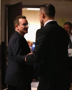 Bono of U2 and Brad Pitt speak backstage during the Oscars held at Dolby Theatre on March 2, 2014 in Hollywood, California.