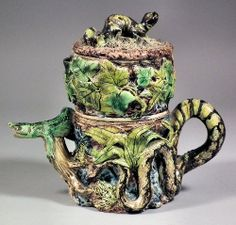 "An unusual 19th Century pottery coffee pot, filter and cover of Palissy Ware design, moulded in bold relief with lizards and frogs, and with snake pattern handle, 7ins high (incised ""L"" to base)"