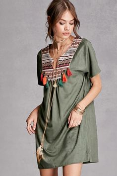A faux suede mini shift dress by Cherry Paris™ featuring a geo-patterned panel on yoke with high-polish trim, burnished medallion accents, contrast tassels, a split neckline with faux suede straps and feather ends, and short sleeves.