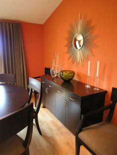 The dark wood dining set and buffet are a sweet complement to pumpkin orange walls in this chic dining room. A gold sunburst mirror echoes the natural tones of the orange walls, while enhancing the overall color scheme. Clear, glass accessories are a neutral accompaniment to the room and avoid interrupting the vibrant wall color.