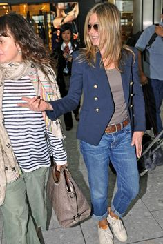 Jennifer Aniston cleaning up a regular jeans and tee look by throwing on a doubled breasted coat. If you don't have a coat use a blazer to achieve the same effect.