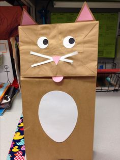 Paper bag cat puppet- smaller egg die, triangles for ears, small triangle for nose, pink 1 inch circle for tongue, 2 white 1 inch circles for eyes, holly berries for pupils, whiskers.