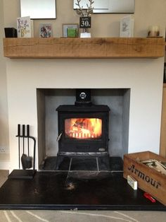 Stove recessed into fireplace with railway sleeper beam