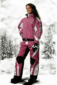 Melanie is wearing a CASTLE pink with black polka dots with white patches on the shoulders,  underarms,  & forearms on her snowmobile jacket;  she's wearing pink with black polka dots with black & white geometric shapes on the thighs and knees on her snowmobile pants.