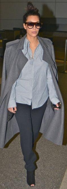 Who made Kim Kardashian's brown sunglasses, gray coat, blue button down top, black boots, and black pants? Coat and sunglasses – Celine  Shirt – Gap  Pants – Kardashian Kollection  Shoes – Tom Ford