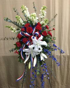 American Flag- white snapdragons, baby blue eucalyptus, red standard carnations, white oriental lilies, blue delphinium, red pixie carnations, blue statice, leather fern and salal fresh flowers with patriotic ribbon weaved throughout the easel design for a funeral