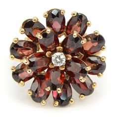 "Vintage Yellow Gold Garnet Ring: This vintage Garnet ring from the Retro period reflects the patriotic/pioneer ""can do"" spirit of that era. Made of yellow gold and set with oval & round Garnet gemstones, this ""wagon wheel"" design complimented the new Western Wear fashions of Joanne Dru and Dale Evans.  Wixon Jewelers"