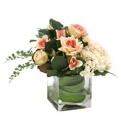 "Add a touch of floral elegance to your credenza or side table with this lovely faux floral arrangement, showcasing delicate rose and hydrangea blooms in a glass vase.   Product: Faux floral arrangementConstruction Material: Polysilk blend and glassColor: Peach and pinkFeatures: Includes faux hydrangeas and rosesDimensions: 12"" H x 13"" W x 12"" DCleaning and Care: Cleans easily with a duster or dryer on cool setting"